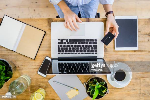 top view of woman at wooden desk with credit card and laptop - e commerce - fotografias e filmes do acervo
