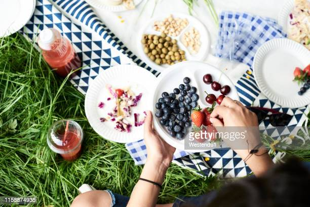 top view of woman eating berries at a picnic in park - picknick stockfoto's en -beelden
