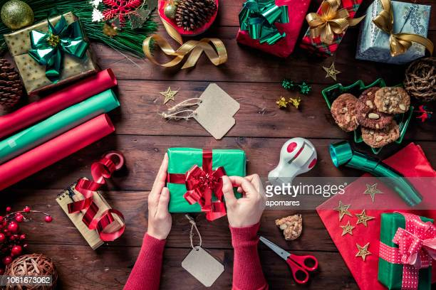 top view of woman hands placing tied bow on gift box. christmas themes. - gift wrapping stock pictures, royalty-free photos & images