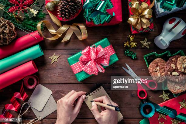 top view of woman hands writing wish list on note pad while wrapping christmas gift box. christmas themes. - list stock pictures, royalty-free photos & images