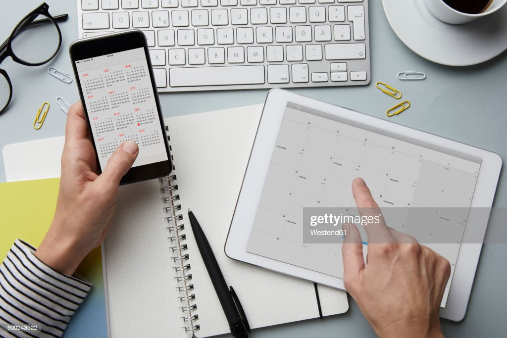 Top view of woman holding smartphone and tablet with calendar on desk : Stock Photo