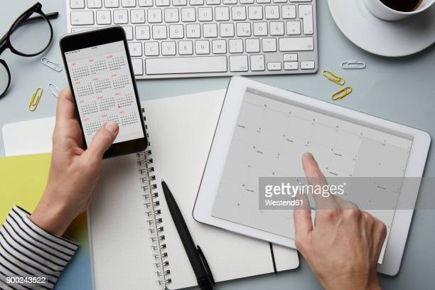 top view of woman holding smartphone and tablet with calendar on desk - temps qui passe photos et images de collection