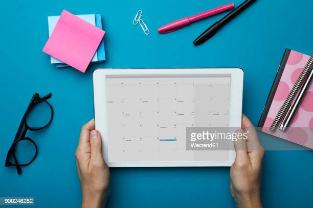 top view of woman holding tablet with calendar on desk - personal organiser stock pictures, royalty-free photos & images