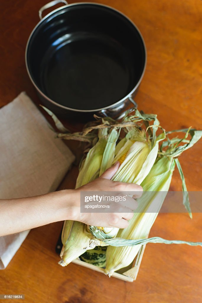 top view of woman prepares corn for cooking in bowl : Stockfoto