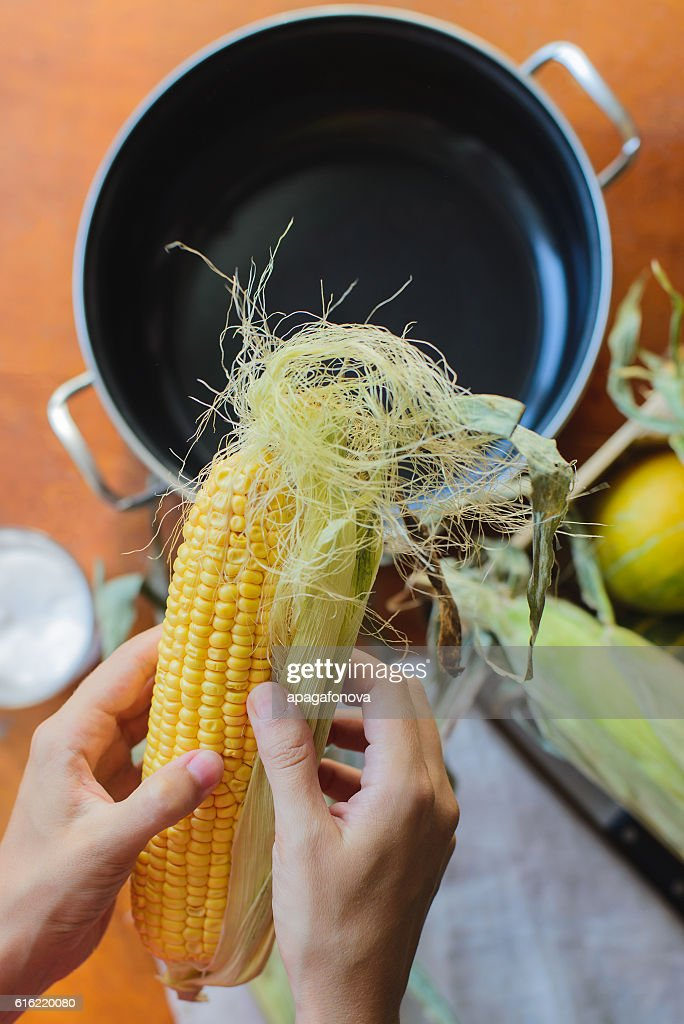 top view of woman prepares corn for cooking in bowl : Photo