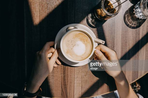 top view of woman sitting by the window in coffee shop enjoying the warmth of sunlight and drinking coffee - routine stock-fotos und bilder