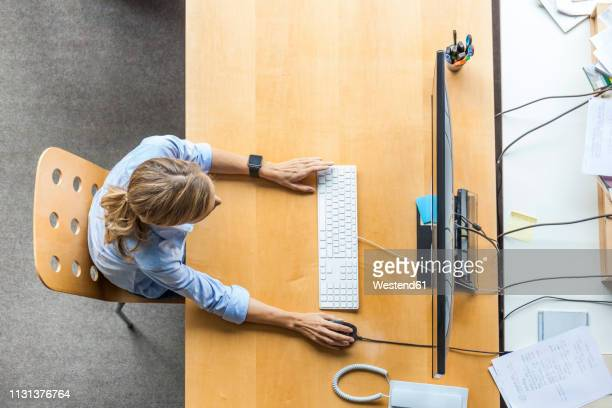 top view of woman using computer at desk in office - looking down stock pictures, royalty-free photos & images