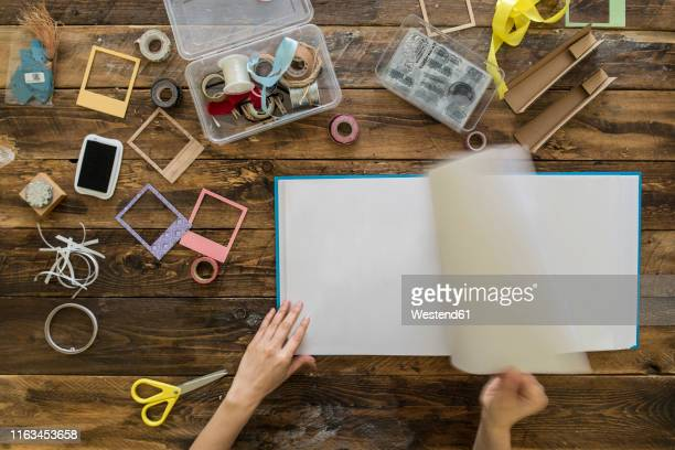 top view of woman's hands preparing a scrapbook - photo album stock pictures, royalty-free photos & images