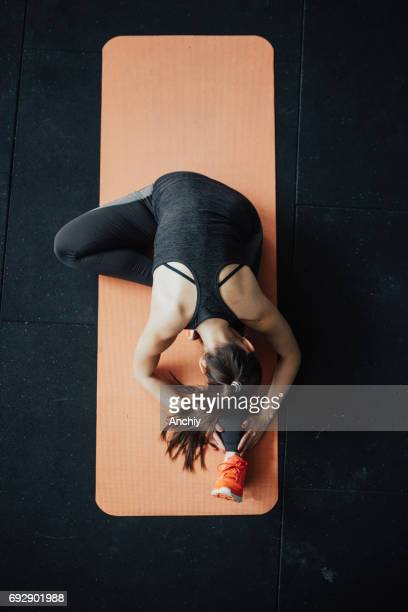 top view of yoga woman in head-to-knee forward bend pose - mat stock pictures, royalty-free photos & images