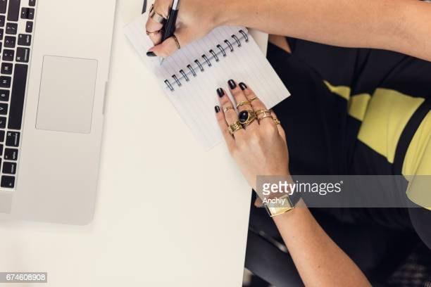 Top view of young business woman writing down notes in her notebook taken from laptop computer
