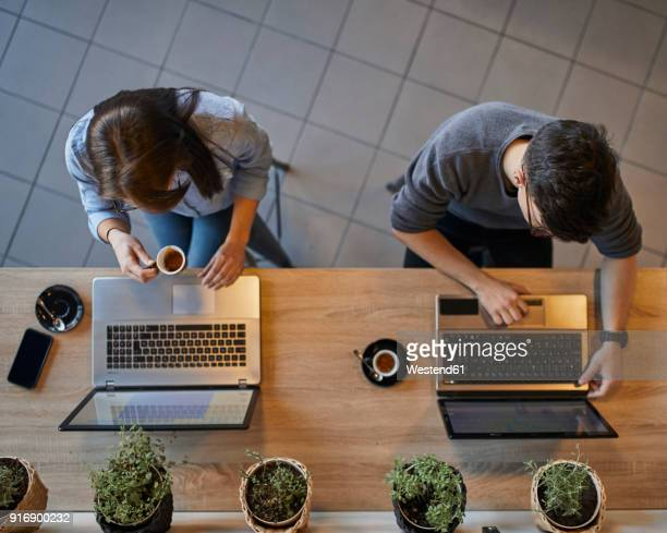 Top view of young woman and man in a cafe using laptops