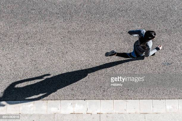 top view of young woman jogging - shadow stock pictures, royalty-free photos & images
