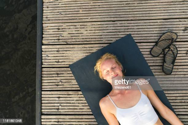 top view of young woman lying on a jetty - sportlichkeit stock-fotos und bilder