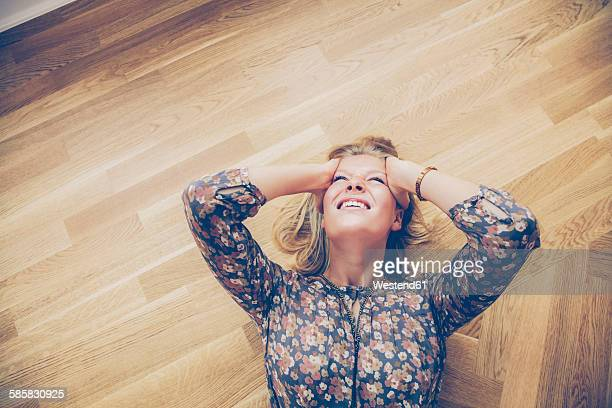 Top view of young woman lying on floor holding her head in pain