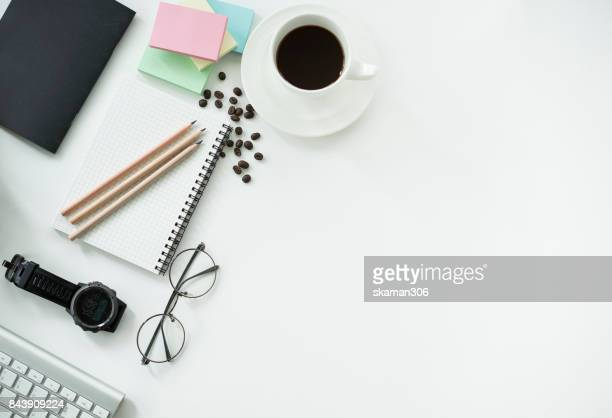 top view Office working desk with Notepad and tablet ,keyboard and sunglasses relaxing drink with coffee cup and roasted coffee seed