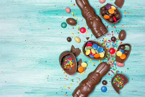 Top view on chocolate traditional easter eggs and bunnies with bright colorful dragee and sugar sprinkles 1128156019