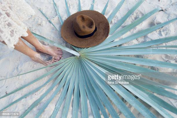 Top view on female feet, brown hat and palm leaf on white sand