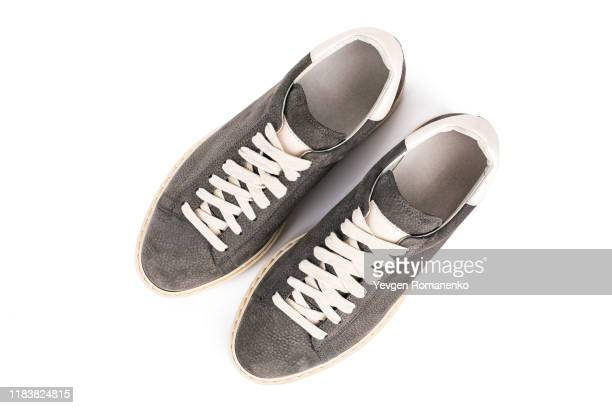 top view on grey suede sneakers shoes on white background, directly above view - white boot stock pictures, royalty-free photos & images