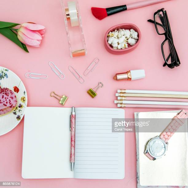 top view pink notebook, beauty brushes, tulips and pink lipstick, hearth shape donut on pink ackground - pink lipstick stock photos and pictures