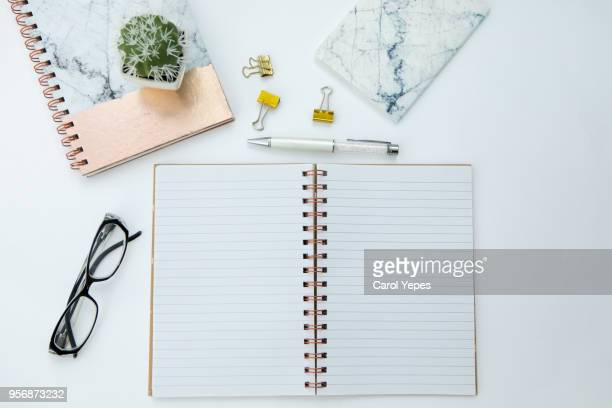 top view pink notebook, pencil, eyeglasses an clips in white background