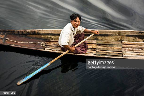 CONTENT] Top view portrait of a fisherman of the Intha tribe paddling his canoe on the black shallow waters of the Inle Lake Shan State Myanmar