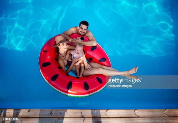top view portrait of young couple with toddler girl in swimming pool outdoors at home. - red tube top stock pictures, royalty-free photos & images
