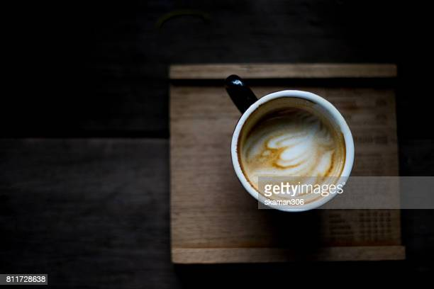 top view selective focus hot cappuccino on wooden plate with darken background
