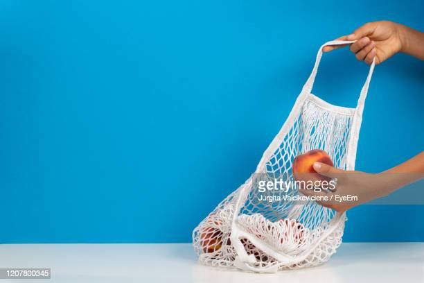 top view to kis hands putting peaches in mesh glocery shopping bag. - blue purse stock pictures, royalty-free photos & images