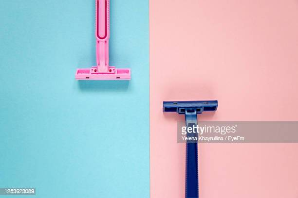 top view two new disposable razors blue and pink on blue-pink background. man-woman relationship - shaved stock pictures, royalty-free photos & images