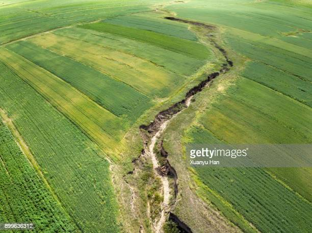 top view-faults and cracks in the farmland - ditch stock photos and pictures