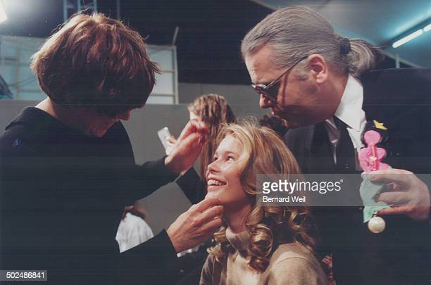 Top while Germanborn Claudia Schiffer has her makeup applied Chanel's designer Karl Lagerfeld shows her the caricature brooch he had made in her image