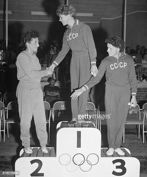Top Women Gymnasts Melbourne Russian gymnast Larisa Latynina who took first place in the women's combined exercises event shakes hands with second...
