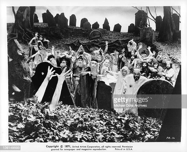 Topal and Norma Crane in a crowd of unknown actors looking as arms are coming out of the earth in a scene from the film 'Fiddler On The Roof' 1971