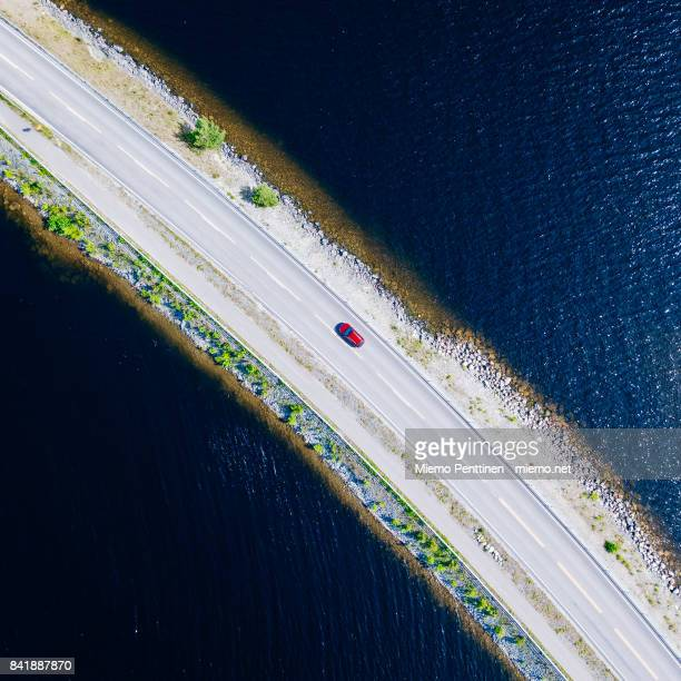 Top-down aerial view into a solitary car driving on a narrow ridge road crossing lake Päijänne in Finland