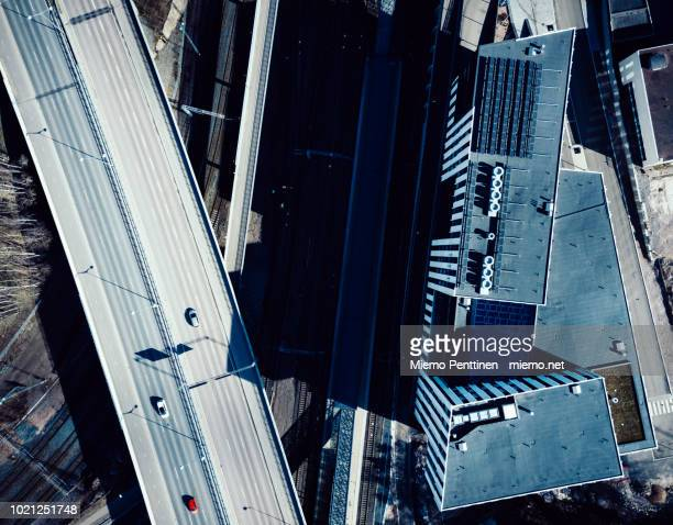 a top-down aerial view into an elevated highway intersection crossing over railway tracks in helsinki - helsinki stockfoto's en -beelden
