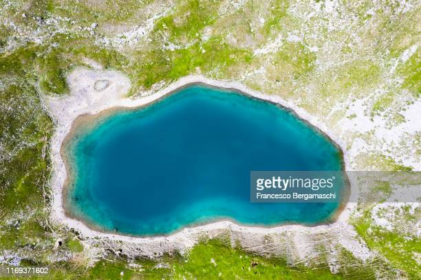 top-down aerial view of a small turquoise lake in the alps - pequeno lago - fotografias e filmes do acervo