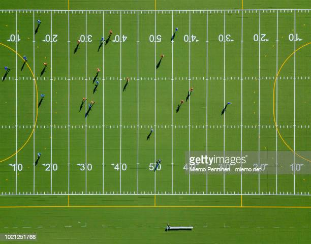 top-down aerial view onto a green american football field with players - football field stock pictures, royalty-free photos & images