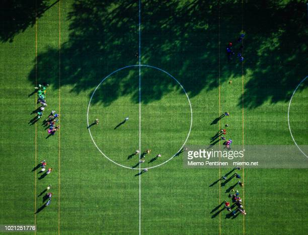 top-down aerial view onto a green soccer field with players gathering - circle stock pictures, royalty-free photos & images