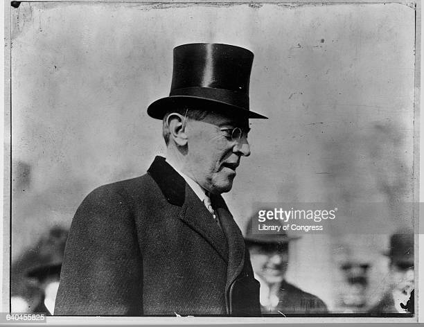 A tophatted US President Woodrow Wilson standing in profile speaks in public Wilson was elected in 1912 and served two terms His second term was...