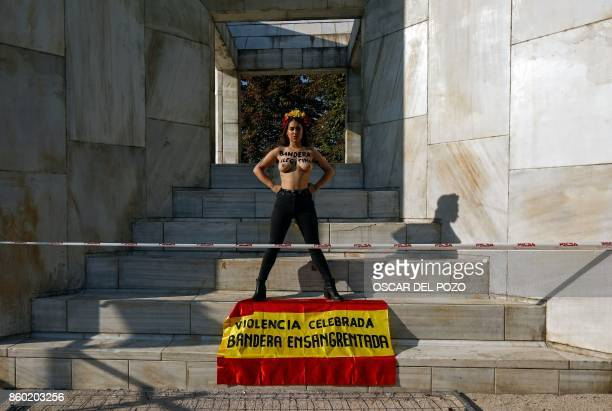 A topless activist of the female right movement of Femen with the text 'Illegitimate flag' written on her chest protests beside a Spanish flag...