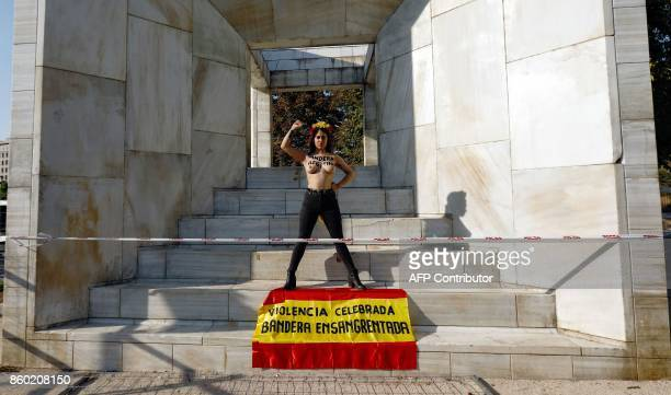 A topless activist of the female right movement of Femen with the text Illegitimate flag written on her chest protests beside a Spanish flag reading...