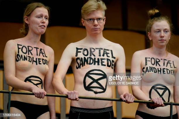 """Topless activists from the global environmental movement Extinction Rebellion have written on their chests """"Tell the Truth"""" as they interrupt a..."""