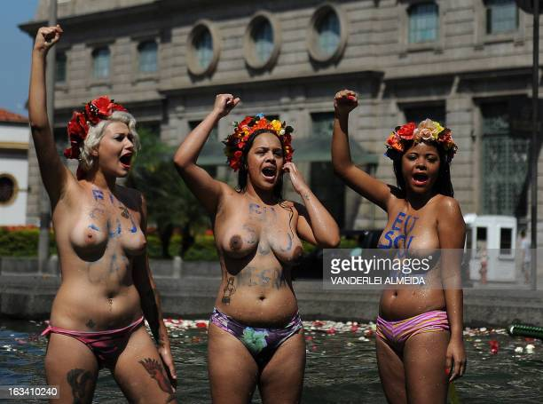 Topless activists of the women's rights group Femen Brazil stage a protest against homophobia at a fountain in front of the Candelaria church in Rio...