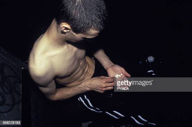 Topless drug dealer holding ecstacy pills in hand UK 1990s