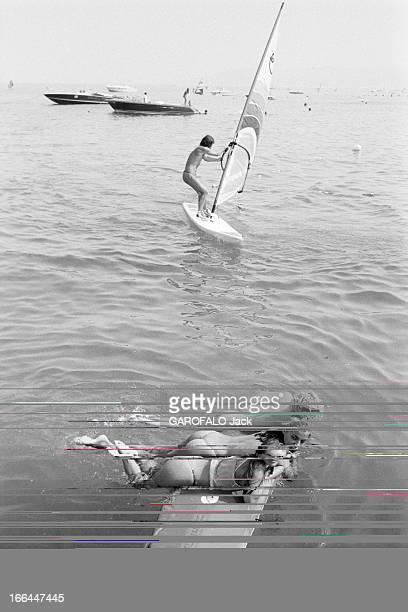 Topless Fashion In SaintTropez En France à SaintTropez en juillet 1983 la mode vestimentaire sur la plage Dans la mer trois jeunes femmes en maillot...