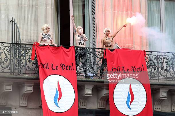 Topless female activists as they demonstrate on a balcony against France's farright Front National political party during FN rally in honor of Jeanne...