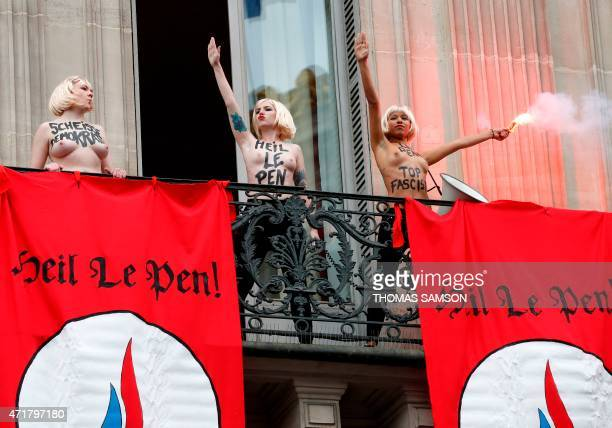 Topless Femen activists perform the Nazi salute and hold up a burning flare near flags reading Heil Le Pen as they demonstrate on a balcony against...