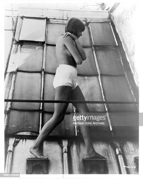 Topless Macha Meril walking on wall steps in a scene from the film 'A Married Woman', 1964.