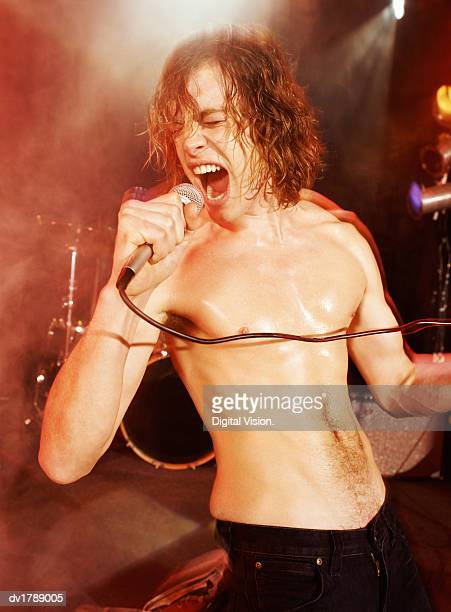 Topless Male Rock Singer Stands on a Spot lit Stage Screaming Into a Microphone