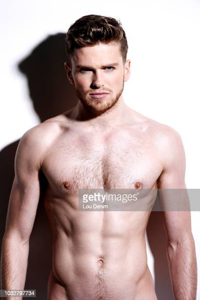 topless man, serious, against a white wall, hard shadow on the wall, looking at the camera - torso stock pictures, royalty-free photos & images